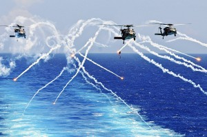 Seahawk helicopters fire flares as they approach the aircraft carrier USS Abraham Lincoln in the Atlantic Ocean, Aug. 2, 2012. (Photo credit: U.S. Navy Seaman Zachary A. Anderson)