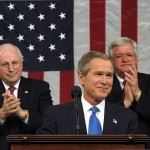 President George W. Bush pauses for applause during his State of the Union Address on Jan. 28, 2003, when he made a fraudulent case for invading Iraq. Seated behind him are Vice President Dick Cheney and House Speaker Dennis Haster