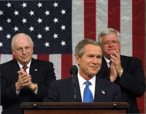 President George W. Bush pauses for applause during his State of the Union Address on Jan. 28, 2003, when he made a fraudulent case for invading Iraq. Seated behind him are Vice President Dick Cheney and House Speaker Dennis Hastert. (White House photo)