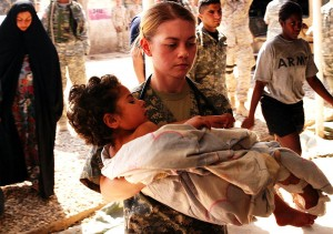 An American soldier carries a wounded Iraqi child to a treatment facility in March 2007. (Photo credit: Lance Cpl. James F. Cline III)