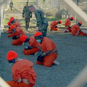Early detainees at the Guantanamo Bay prison, dressed in orange jumpsuits with goggles covering their eyes, photographed on Jan. 11, 2002. (Defense Department photo by Petty Officer 1st class Shane T. McCoy, U.S. Navy)