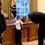 President Barack Obama bending over so a boy visiting the Oval Office could feel that the President's hair was like his. (White House photo by Pete Souza)