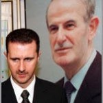 Syrian President Bashar al-Assad in front of a poster of his father, Hafez al-Assad.