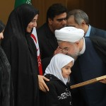 Iran's President Hassan Rouhani celebrates the completion of an interim deal on Iran's nuclear program on Nov. 24, 2013, by kissing the head of the daughter of an assassinated