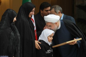 Iran's President Hassan Rouhani celebrates the completion of an interim deal on Iran's nuclear program on Nov. 24, 2013, by kissing the head of the daughter of an assassinated Iranian nuclear engineer. (Iranian government photo)