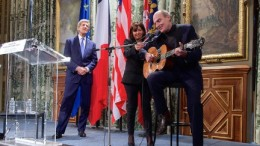 """Singer James Taylor performs """"You've Got a Friend"""" onstage in Paris on Jan. 16, 2015, during a tribute to the victims of the Charlie Hebdo massacre. On the left is Secretary of State John Kerry. (U.S. State Department photo)"""