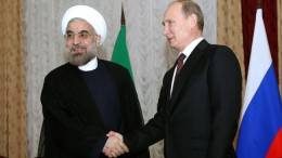 Iranian President Hassan Rouhani (left) shakes hands with Russian President Vladimir Putin at the Shanghai Cooperation Organization summit in the Kyrgyz capital of Bishkek on Sept. 13, 2013. (Photo credit: Press TV)