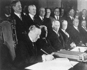 U.S. Pres. Calvin Coolidge (seated left) signing the Kellogg-Briand Pact, January 1929, Washington, D.C. (Photo Credit: Keystone/Hulton Archive/Getty Images)