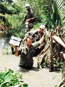 Don North of ABC News crossing stream in Mekong Delta with US Army 9th Division.