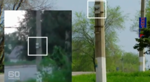 "A screen shot from Australia's ""60 Minutes"" update supposedly showing a utility pole in the ""getaway"" video and matching it up with a poll in an intersection of Luhansk in eastern Ukraine. However, note that the inset obscures the spot where a house appeared on the original video."