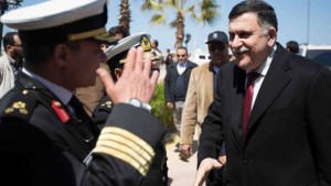 "Prime Minister Fayez Sirraj of the Libya's new ""unity government,"" as selected by U.N. and U.S. officials, is welcomed by naval officers after landing in Tripoli."