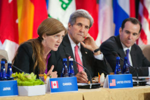 U.S. Ambassador to the United Nations Samantha Power flanked by U.S. Secretary of State John Kerry delivers remarks at the Pledging Conference in Support of Iraq at the U.S. Department of State in Washington, D.C. on July 20, 2016. [State Department Photo/ Public Domain]