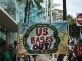 Protest signs urging global conservation meeting to address the environmental damage from U.S. military bases. (Photo by Ann Wright)