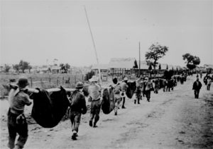 Filipino and U.S. prisoners of war use improvised litters to carry fallen comrades at Camp O'Donnell, Capas, Tarlac, 1942, following the Bataan Death March. (Wikipedia)