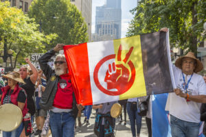 Activists carry the American Indian Movement flag at a protest against the Dakota Access Pipeline. (Flickr John Duffy)