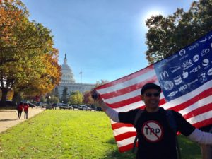 An activist wearing an anti-TPP shirt and holding a US flag with corporate logos instead of stars celebrates the defeat of the TPP at a rally on November 17, 2016. (Photo by Chelsea Gilmour)