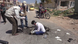 Photograph of men in Khan Sheikdoun in Syria, allegedly inside a crater where a sarin-gas bomb landed.