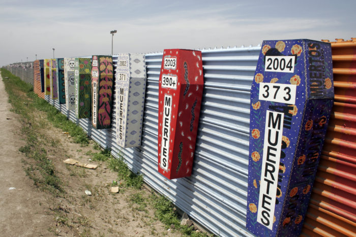 Memorial coffins on the US-Mexico barrier for those killed crossing the border fence in Tijuana, México. (Tomas Castelazo, Wikimedia)