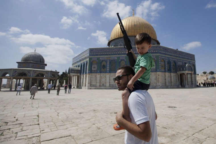 Palestinian man with a child holding a fake gun outside the Dome of Rock at the Al-Aqsa Mosque compound, Islam's third most holy site, in 2013, after disturbances that caused the temporary closure to the mosque. (Jordi Bernabeu Farrús via Flckr)