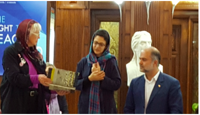 Barbara Briggs-Letson presenting the book to Tehran Peace Museum Director Taghipour and Peace Education Department & Translator Yalda Khosravi. (Jodie Evans)