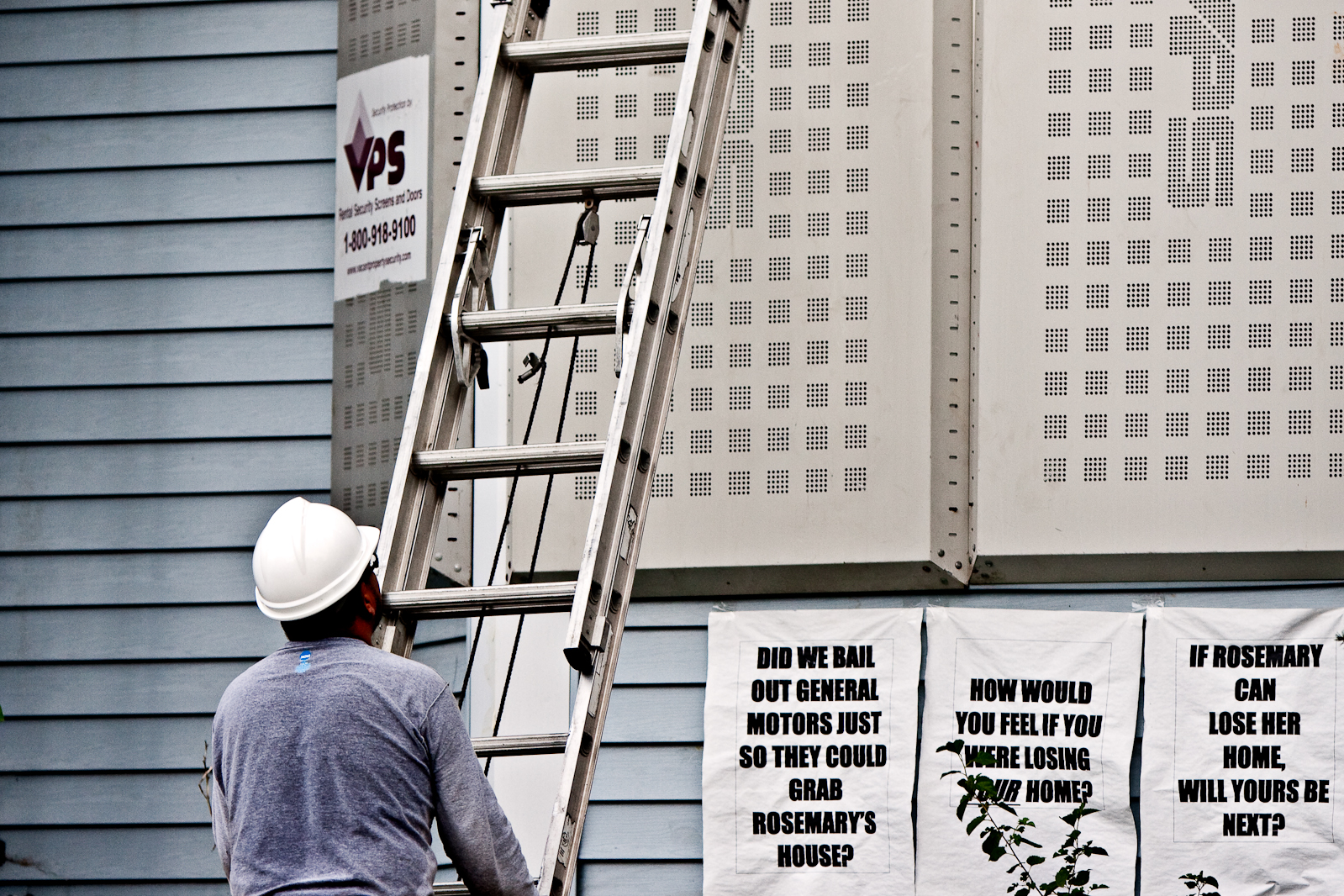 Worker installs security panels over windows after police evict woman from her foreclosed home in South Minneapolis, 2009. (Tony Webster, CC BY 2.0, Wikimedia Commons)