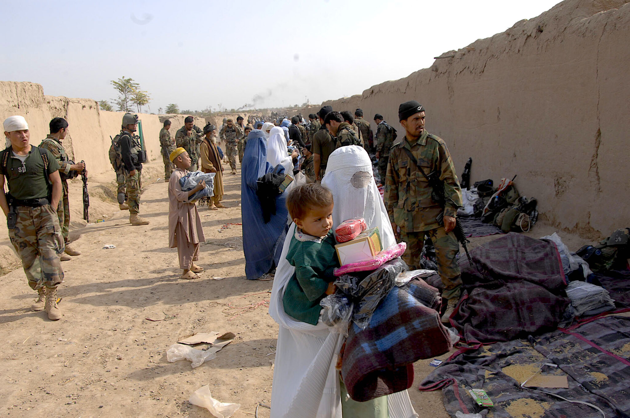 Afghan soldiers hand out supplies to Afghans who had been evicted from their villages by Taliban fighters in Konduz, Afghanistan, Nov. 6, 2009. (U.S. Army/Spc. Christopher Baker)