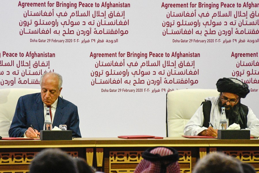 Khalilzad signs peace deal with  Taliban, next to Mullah Abdul Ghani Baradar, the group's top political leader, in Doha, Qatar, Feb. 29, 2020. (J.P. Lawrence/ STARS AND STRIPES/DOD)