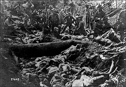 US soldiers pose with Filipino Moro dead after the First Battle of Bud Dajo, March 7, 1906, Jolo, Philippines. (Wikimedia Commons/Unknown Author)